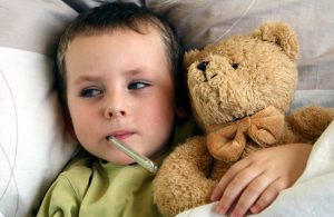 Young child with thermometer and sweet taddy lying in bed with flu and fever. Child with a temperature.